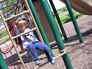 ребенок на качелях детской площадки